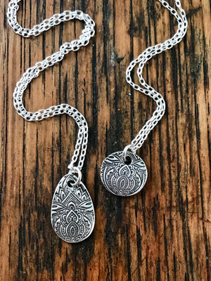 small patterned silver circle teardrop pendant on a thin sterling silver chain