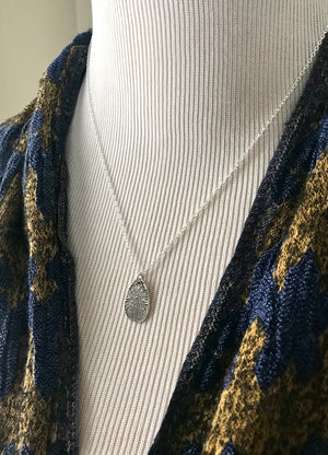 small patterned silver teardrop pendant on a thin sterling silver chain