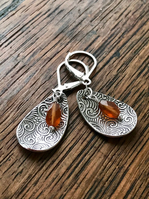 cupped silver teardrop shaped lever back earrings with swirl design and hessonite garnets