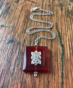square burnt orange carnelian bead frame necklace with an ornate silver bead at its center