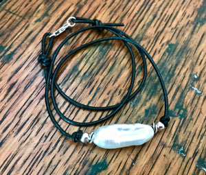 thin black leather cord with a long horizontal stick pearl pendant with silver accent beads
