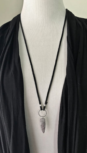 black deerskin leather cord necklace with a silver tribal shield pendant hanging from a silver twisted ring