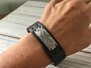 leather cuff with an embossed silver bar stitched to it with waxed linen thread