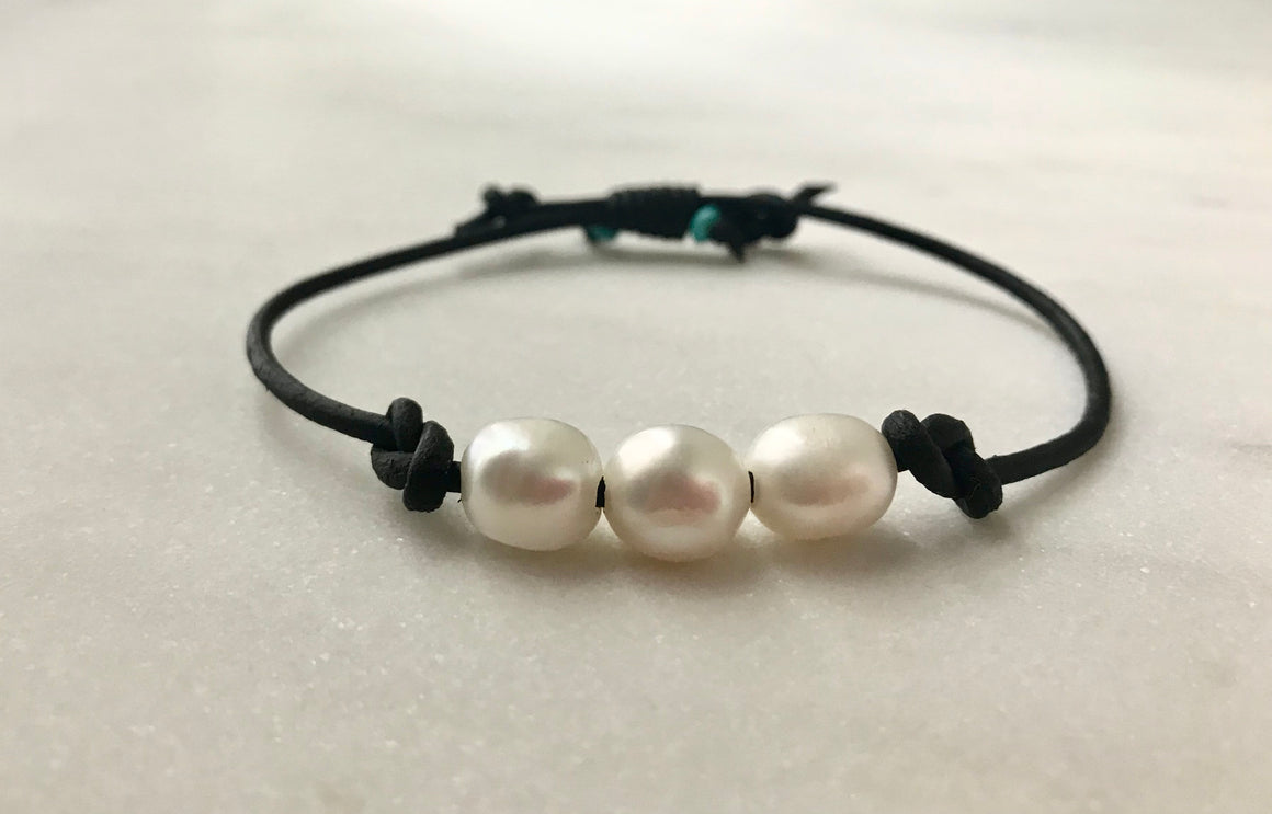 adjustable bracelet with three white pearls knotted on thick black leather cord