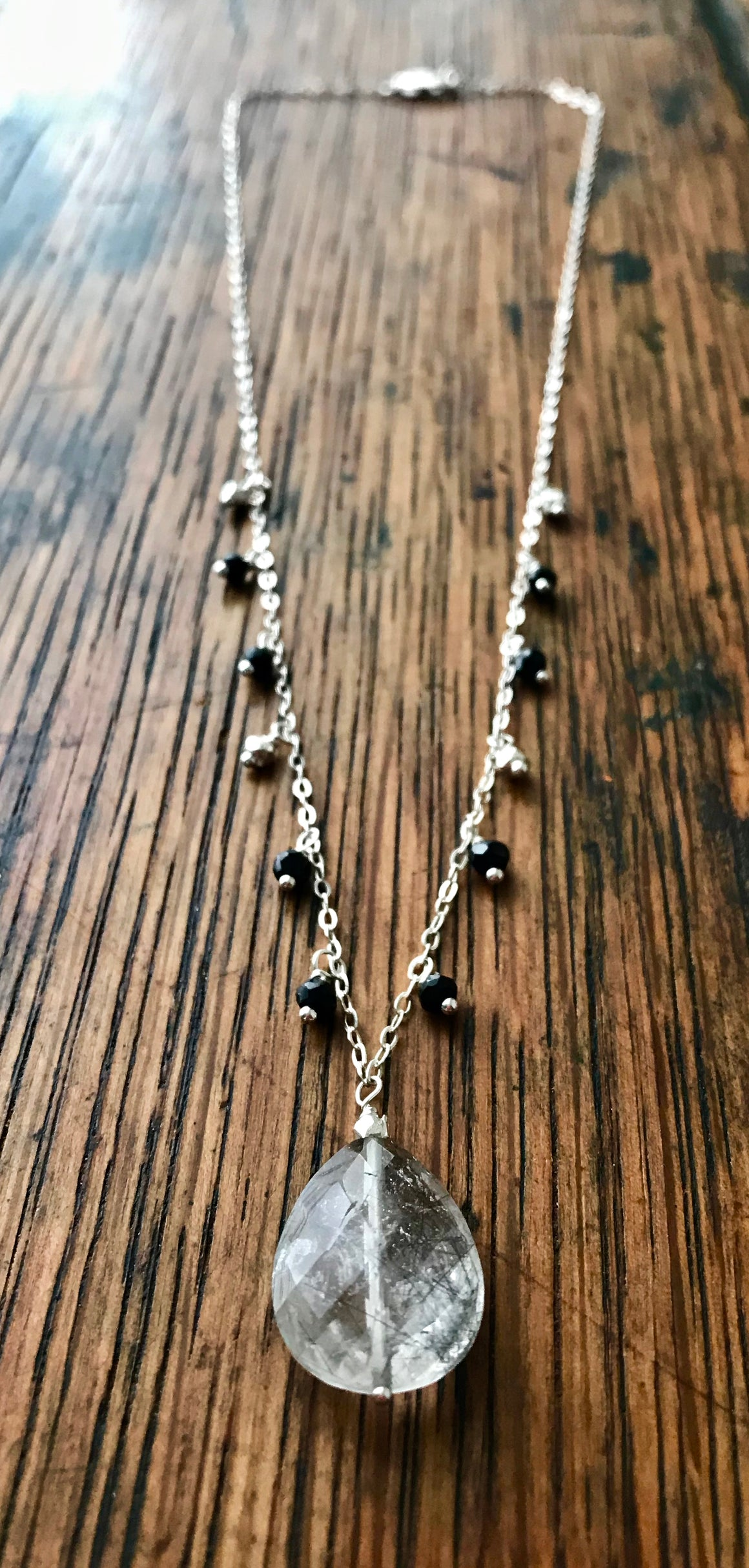 large faceted rutilated quartz teardrop on chain with black and silver drops