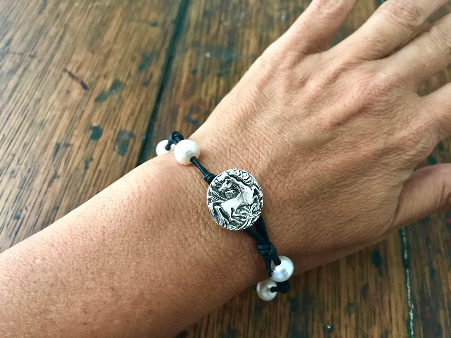 black leather cord and white pearl bracelet with a horse themed circular silver button clasp
