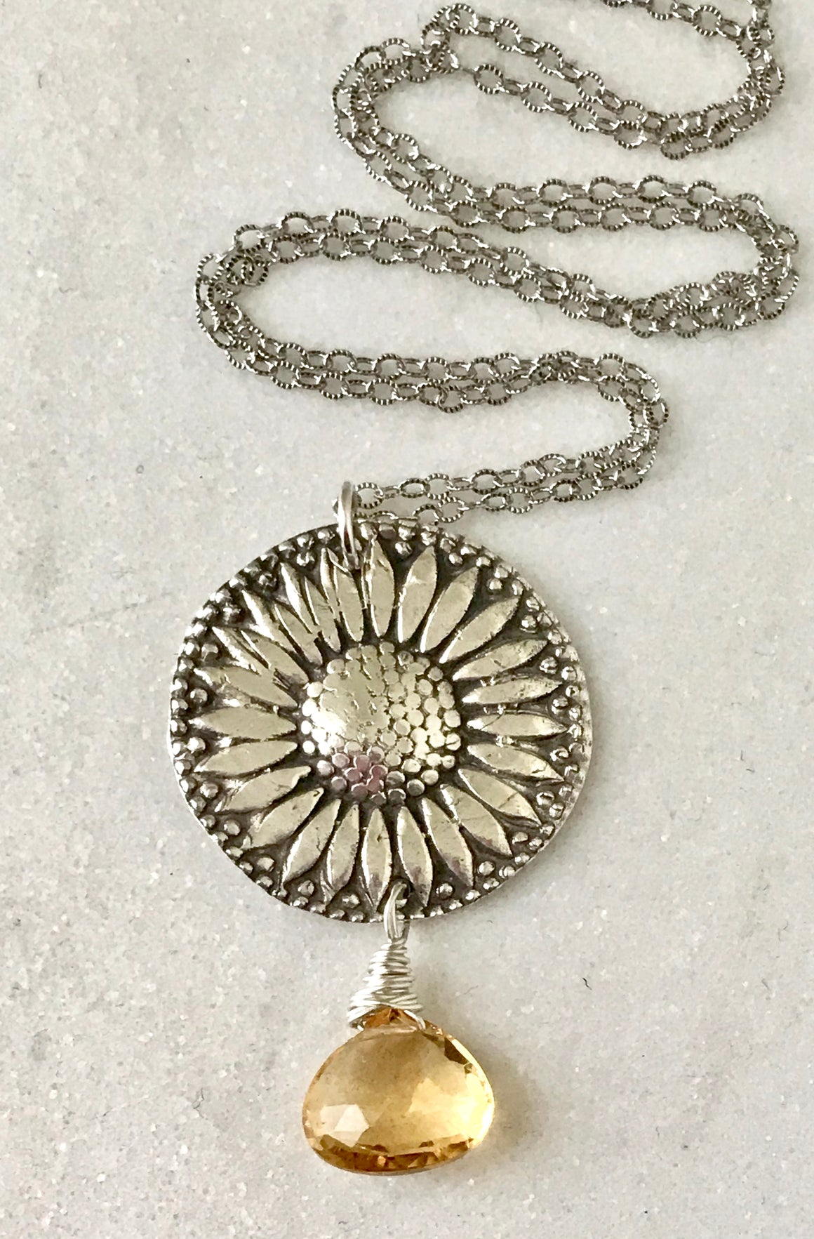 large silver sunflower pendant with a faceted golden yellow citrine gemstone teardrop