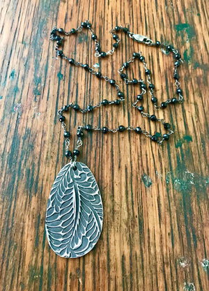 large deeply embossed silver fern pendant on a chain of small wire wrapped black spinel gemstones