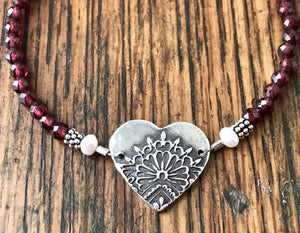 Faceted red garnet gemstone bracelet with a silver mandala heart