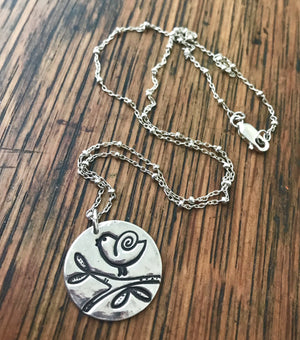 beaded silver chain necklace with a circular singing bird pendant