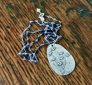periwinkle iolite rosary chain necklace with a large embossed egg shaped silver flower pendant