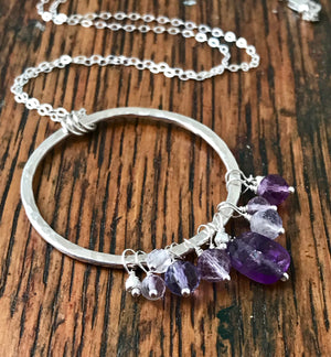 purple gemstones wire-wrapped on a large hammered silver hoop pendant
