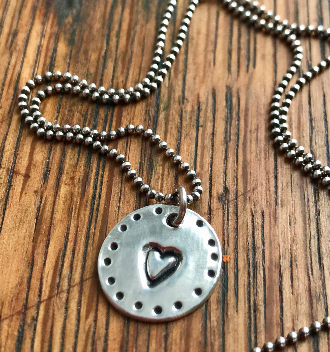 small silver circle pendant stamped with a heart on sterling silver ball chain