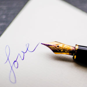 "alt=""word Love written in cursive and a golden calligraphy pen"""