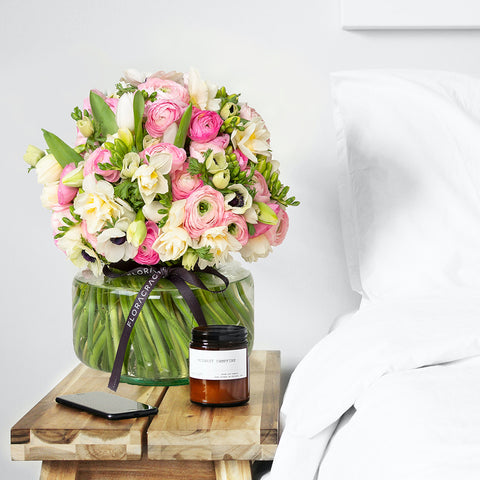 "alt=""pink Floracracy arrangement on a nightstand in a white bedroom"""
