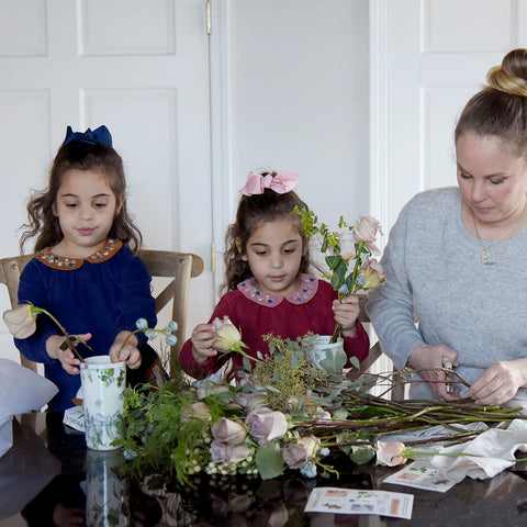 "alt=""mom and daughters play with floral bundle"""
