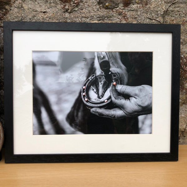 black and white image in a black frame of a farrier 'nailing the hind' on a horseshoe
