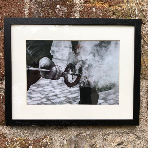 Black and white image in a black frame of a farrier burning a shoe onto a horse.