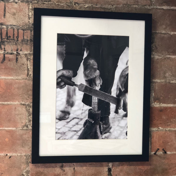 black and white image in a black frame of a farrier 'rasping the hoof'