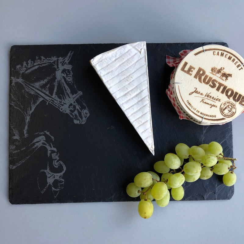 Black Slate cheeseboard with horse etched on featuring a block of brie and some grapes