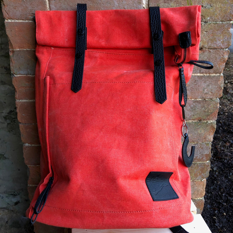 Red waxed backpack with black leather straps and black leather logo of a horse