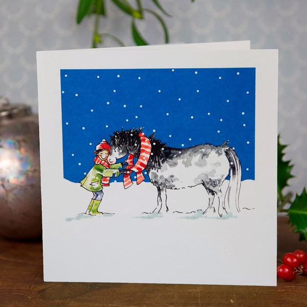 Christmas card with a horse and girl wearing matching scarves in the snow
