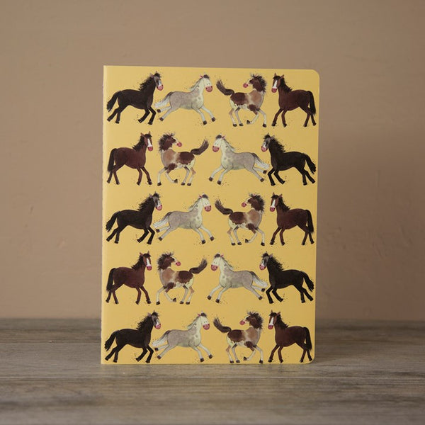 Large yellow notebook with running horses printed on