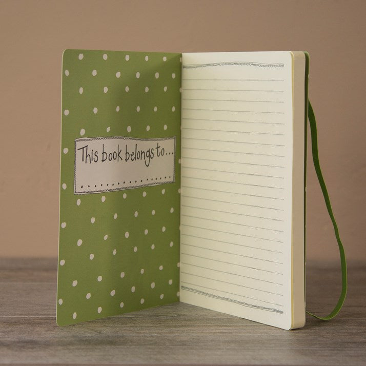 Lined page of journal with spotty inside cover saying 'this book belongs to...'