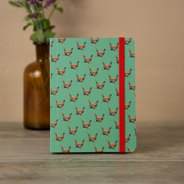 Green Alex Clark notebook with a repeated pheasant pattern and red elastic holding the book shut