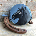 Blue round coin purse with black horse head on the front