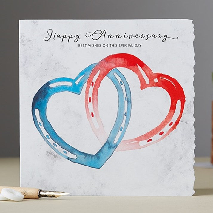 Happy Anniversary Card with 2 interlocked horseshoes in heart shaped. one blue and one red.