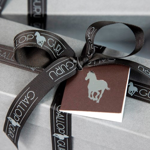Grey gift box, tied with brown Gallop Guru ribbon and finished with a chocolate gift tag with grey horse on front