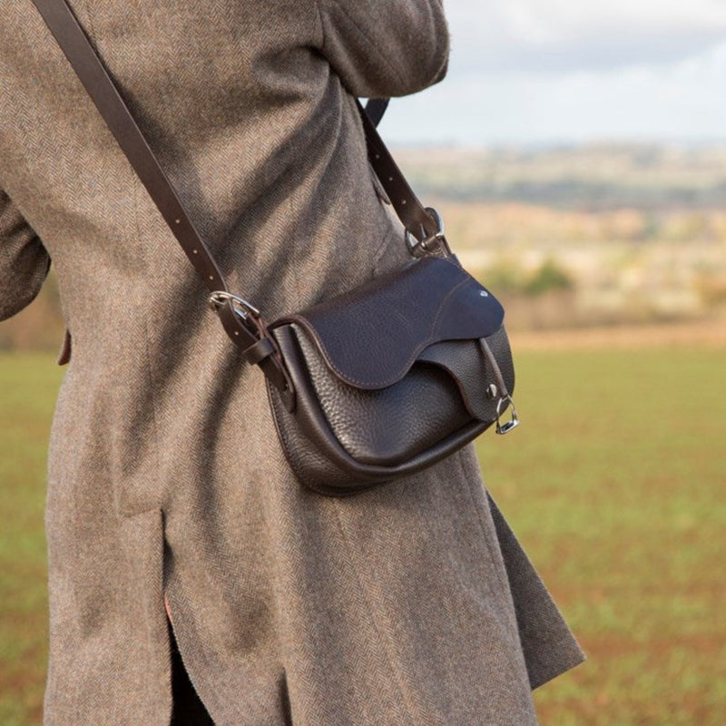 Woman wearing leather saddle handbag in the countryside