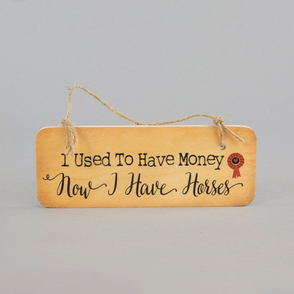 Wooden hanging sign with 'i used to have money, now i have horses' printed on
