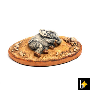 Top view of the collectable portraying a baby elephant lying down. Buy this African gift now.