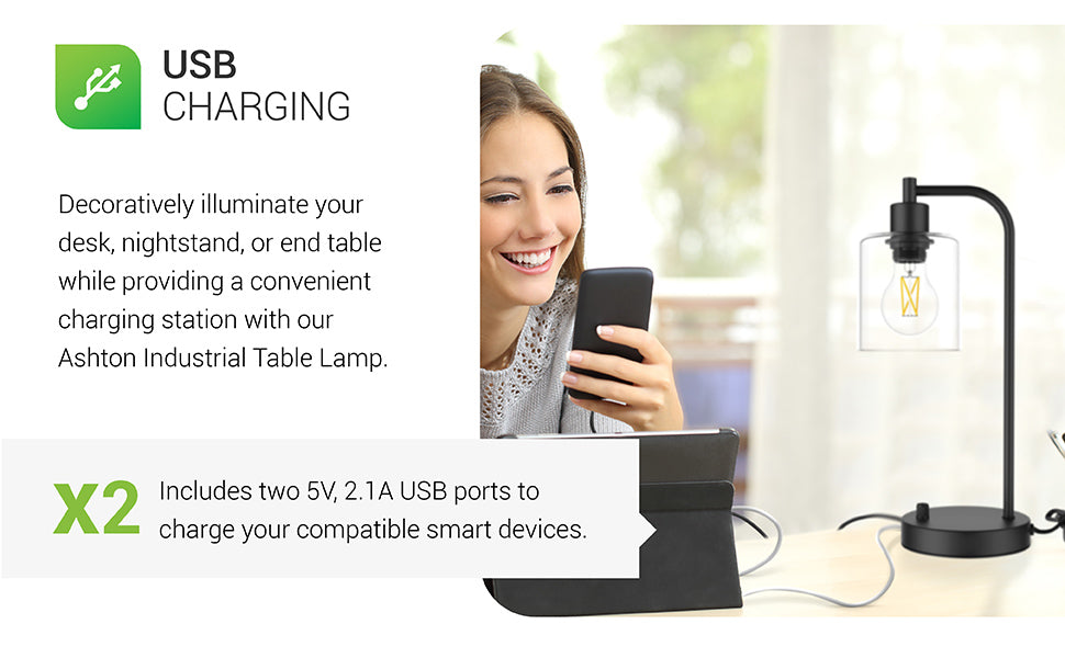 USB Charging. Decoratively illuminate your desk, nightstand, or end table while providing a convenient charging station with our Ashton Industrial Table Lamp. Includes two 5V, 2.1A USB ports to charge your compatible smart devices. Fixture includes a glass shade to show off the popular filament bulb inside. Image is of a woman looking at her phone and tablet while both charge with the dual USB ports on the lamp base.