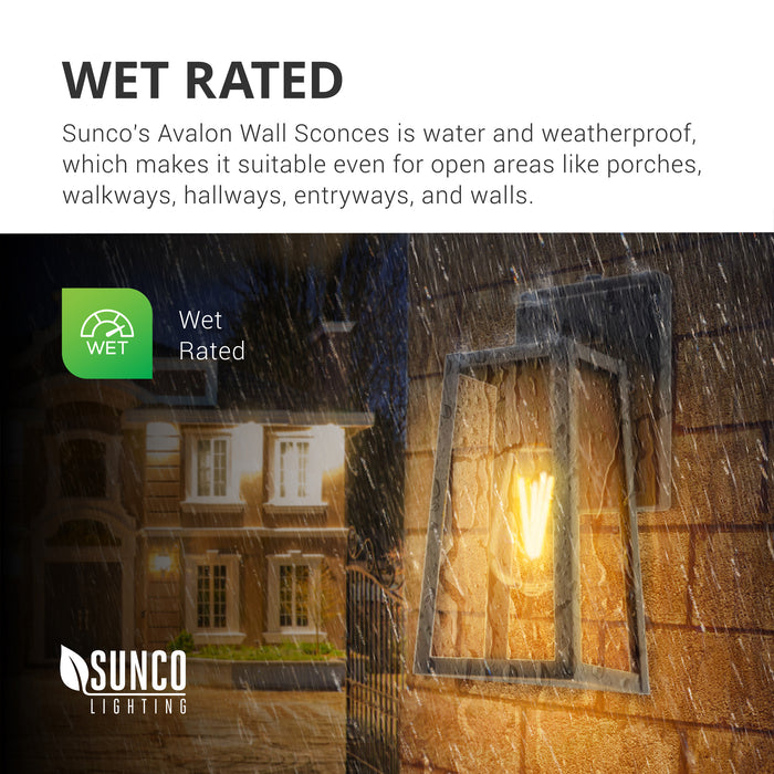 Wet Rated. Sunco's Avalon Caged Wall Sconce with Dusk to Dawn technology is water and weatherproof. It is suitable for open areas like porches, walkways, hallways, entryways, and walls both inside and out. Image features the Avalon Caged Wall Sconce with ST64 LED Filament Bulb on the exterior of a home with rain falling. You can clearly see the LED filament bulb inside the black, durable frame.