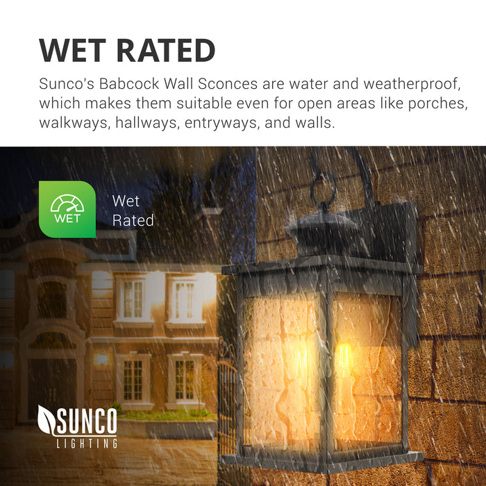 Wet Rated lighting fixture. Sunco Babcock Wall Sconces are water and weatherproof. This makes them suitable for porches, walkways, hallways, entryways, and exterior walls like the one seen here. Image shows the Babcock Wall Sconce with its clear, glass panes and dual candelabra lights sockets with a B11 LED Filament (sold separately) inside while rain splashes on the wall and wall sconce.