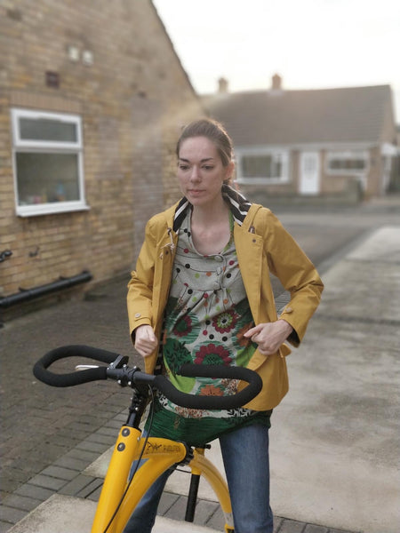 Photo of a person wearing a yellow coat, looking down, standing over the yellow frame of an Alinker. The handlebars appear at the lower-front of the photo.