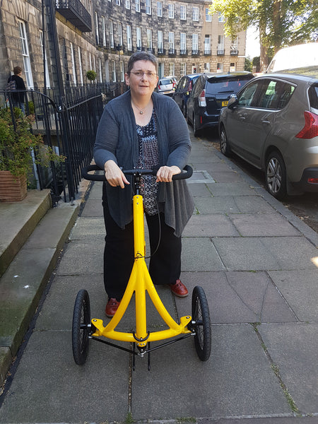 A person using an Alinker to walk down a city footpath. She is facing the camera and you can see parked cars and terraced houses in the background.