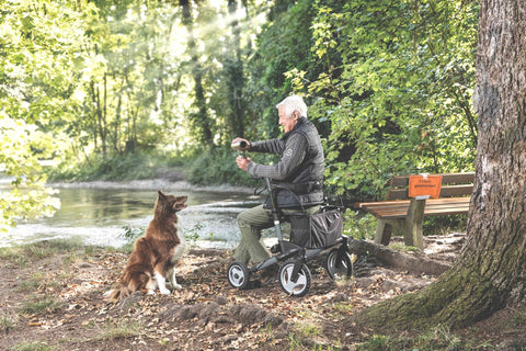 Man sitting on Topro 2-in-1 rollator/wheelchair near riverbank, with dog