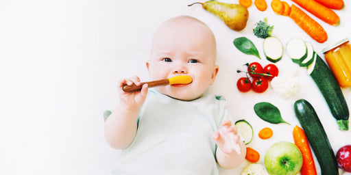Healthy child nutrition, food background, top view. Baby 8 months old surrounded with different fresh fruits and vegetables on white background. Baby first solid feeding