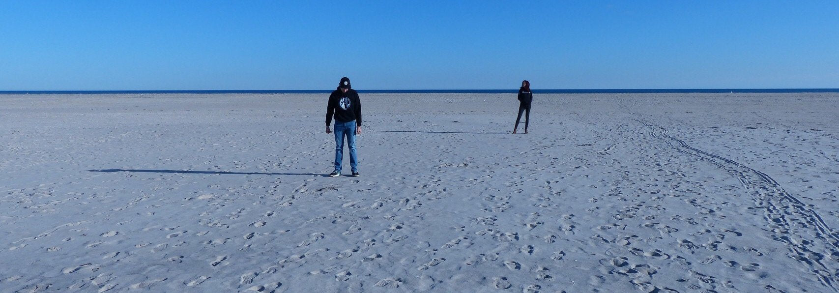 Man in the front of the image, woman in the background, wearing GFL sweaters on the beach