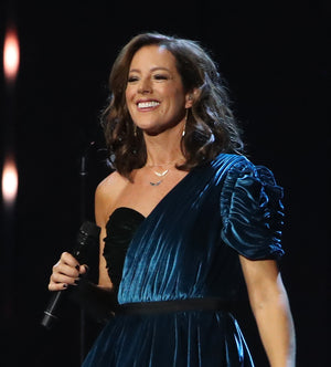 SARAH MCLACHLAN WEARING YELLOW GOLD BLACK DIAMOND AND YELLOW GOLD WHITE DIAMOND ANGEL WING NECKLACES