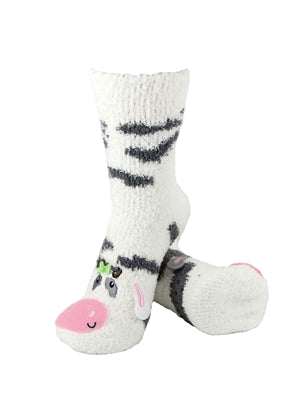 One pair of white fuzzy socks. There is a playful cow face stitched into the top of the foot section of the sock, and black spots across the rest of the sock. The sock is crew length, going a few inches over the ankle.