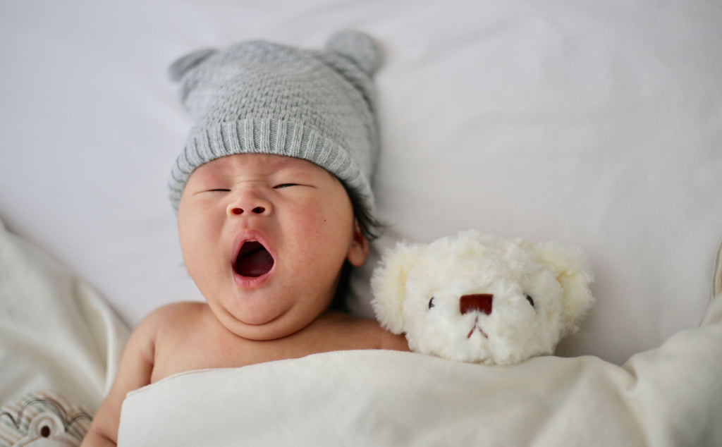 Baby in bed with his teddy. Grey woollen hat, white teddy.