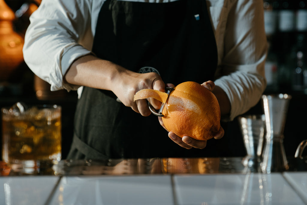 Man in a bar making a cocktail with whiskey