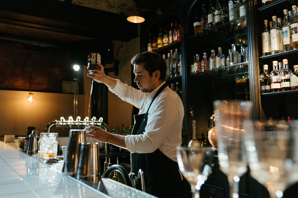The man at the bar pours whiskey into a unbreakable tritan glass