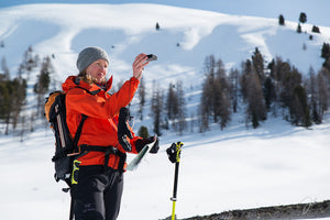Woman looking into the sighting tools of the Suunto MB-6 Global compass