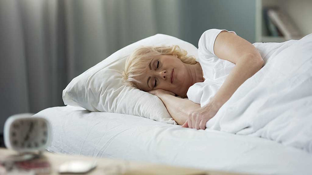 Attractive mature female sleeping in bed